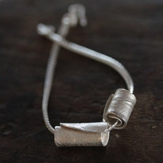 Silver bracelet with two handmade wrapped rolls with textured surface