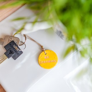 "The yellow key chain(key ring) with the word "" Be Charming ""."