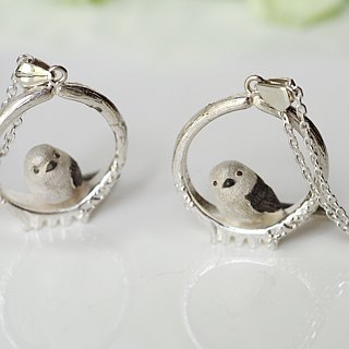 A pendant white finish of a plumping bird (Robin) stuck in a branch