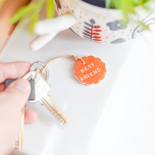 "The orange key chain(key ring) with the word "" Best Friend ""."