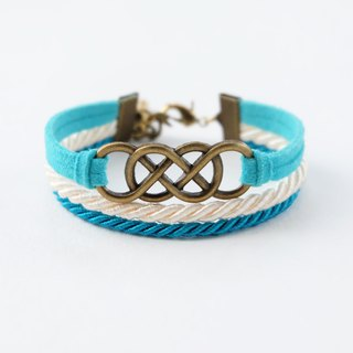 Brass double-infinity in Candy blue suede / Cream / Peacock blue
