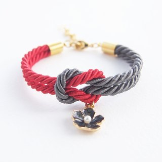 Red and dark gray knot rope bracelet with black flower charm