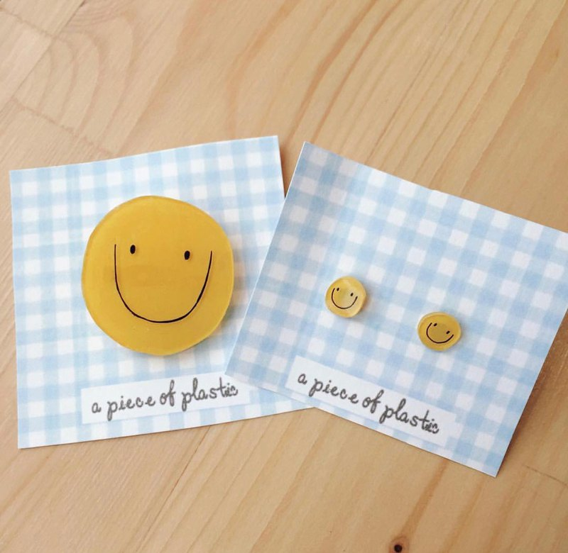 Seth brooch and smiley face earrings